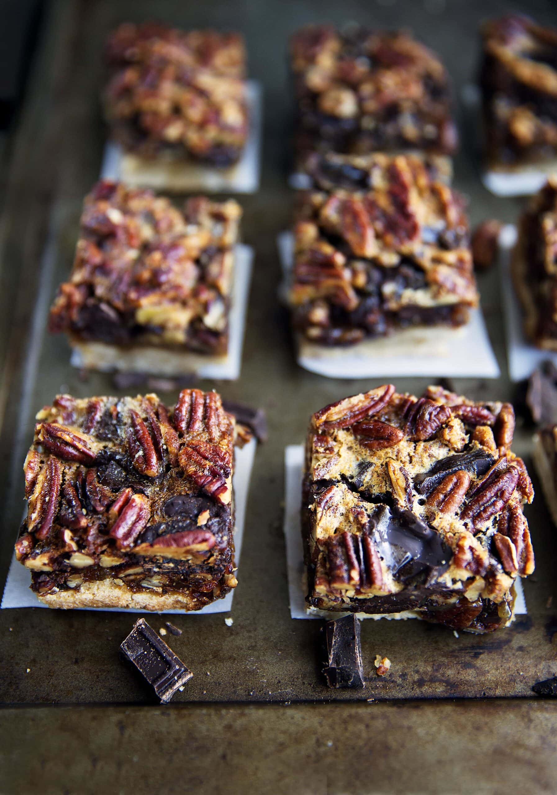 Thanksgiving is just around the corner. These Bourbon Chocolate Pecan Pie Bars will become your family's favorite recipe for years to come! | via Broma Bakery | #pecanpie #bourbonpecanpie #bars