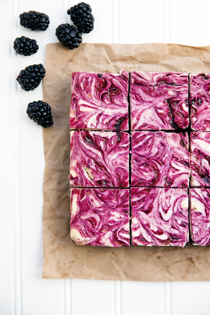 Blackberry cheesecake brownies sliced on parchment paper