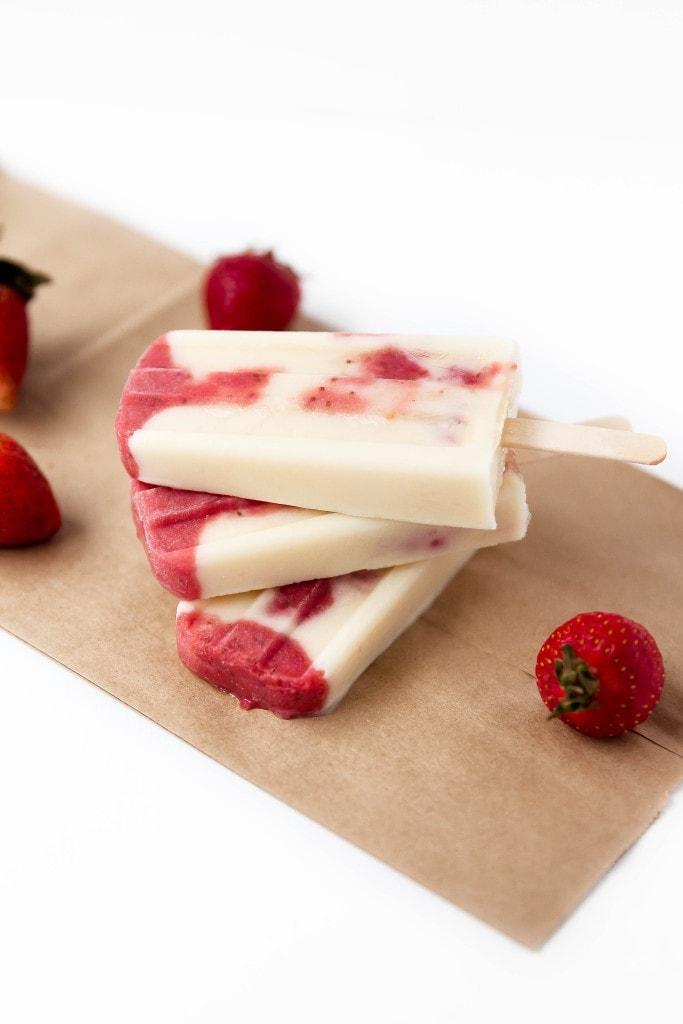 Skinny Strawberries and Cream Popsicles: layers of roasted strawberries and greek yogurt make these popsicles a bikini-welcome summer treat!