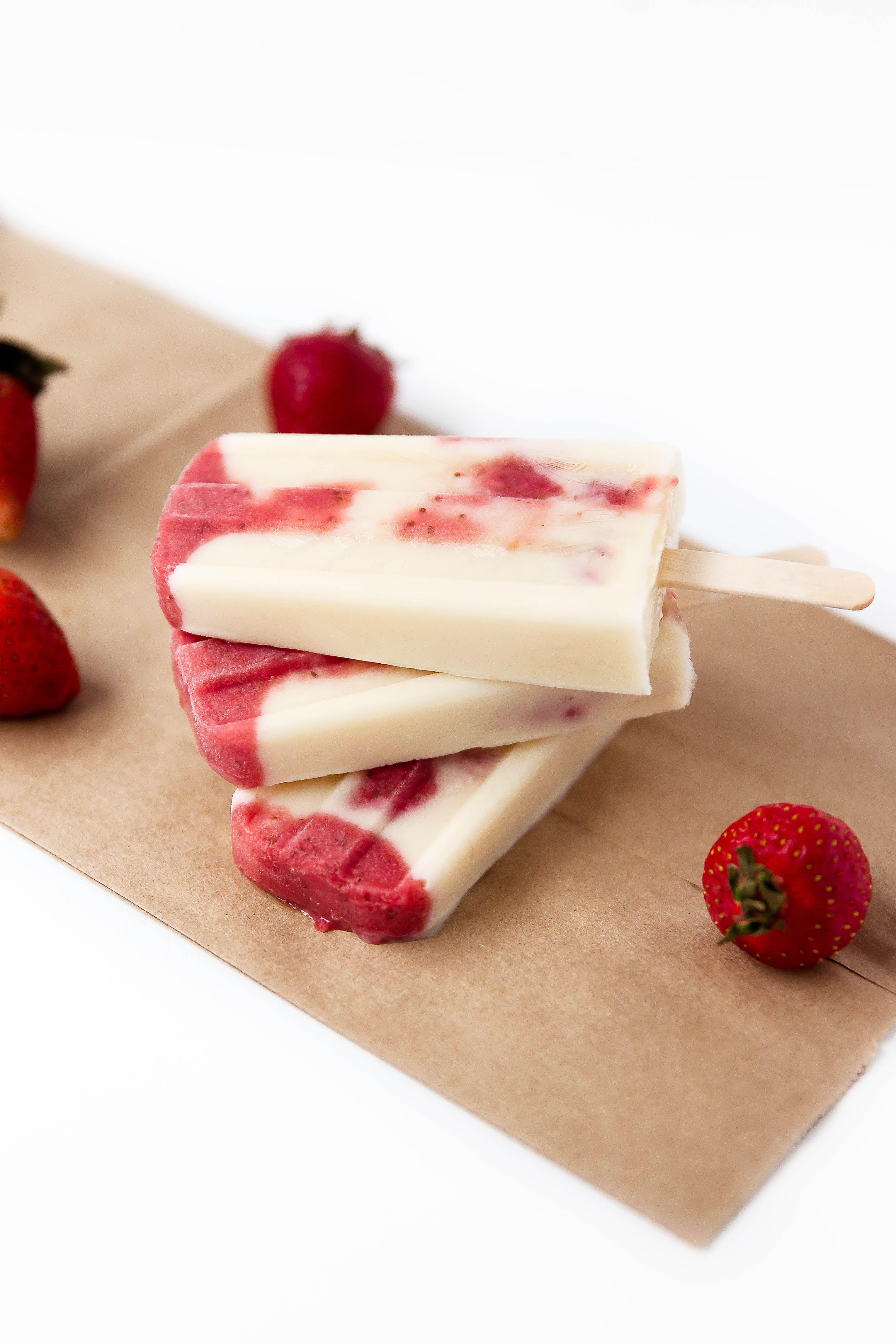 Skinny Strawberries and Cream Popsicles: layers of roasted strawberries and greek yogurt make these popsicles a bikini-welcome summer treat!