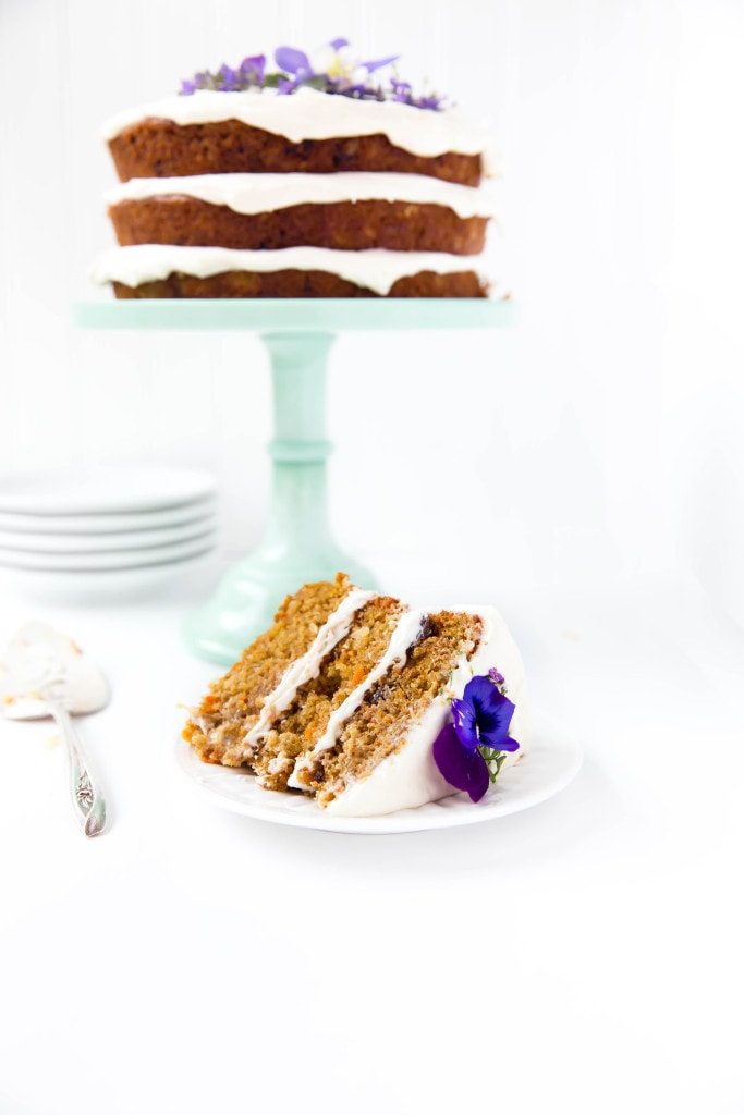 slice of carrot cake in front of cake on stand