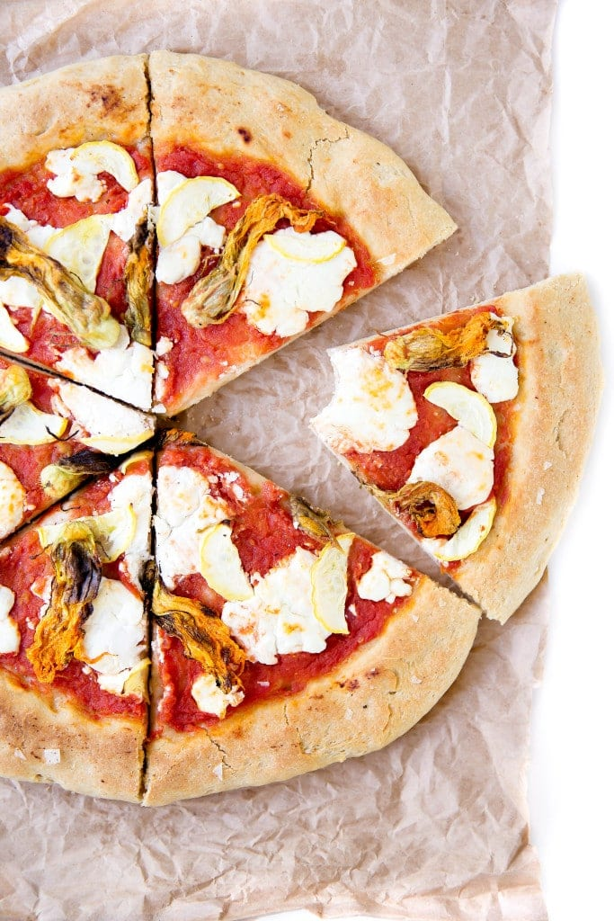 A perfect summer pizza made with crushed tomatoes, mozzarella, and squash blossoms!