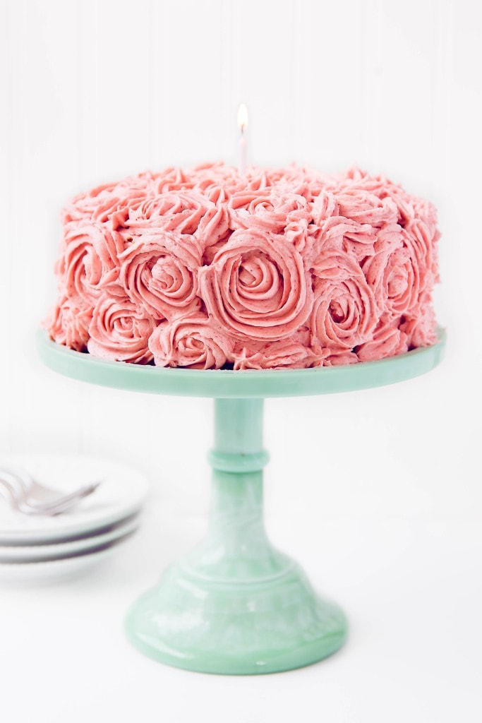 Almond Strawberry Cake with Strawberry Buttercream on a cake stand