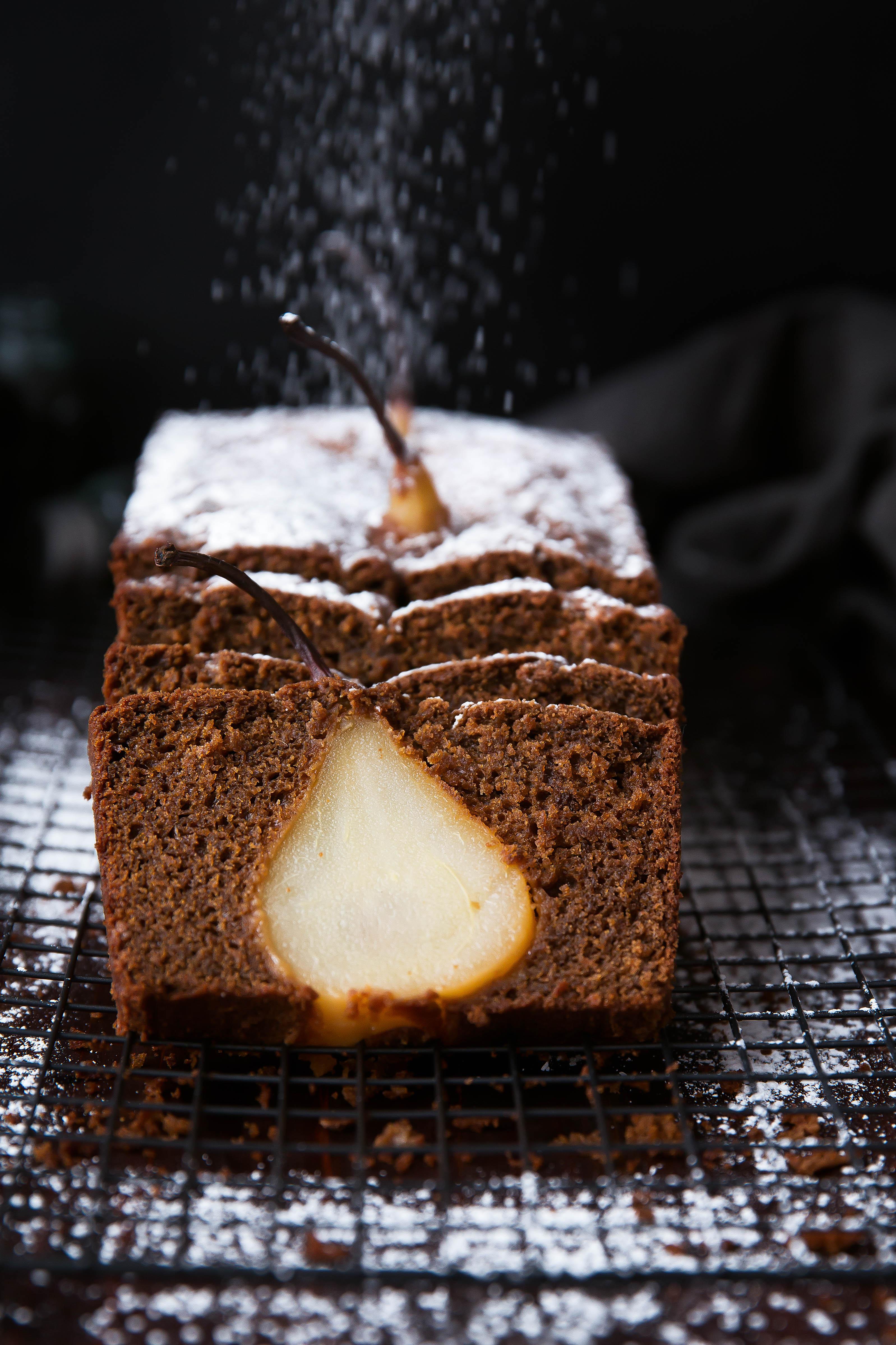 sprinkling powdered sugar onto gingerbread loaf