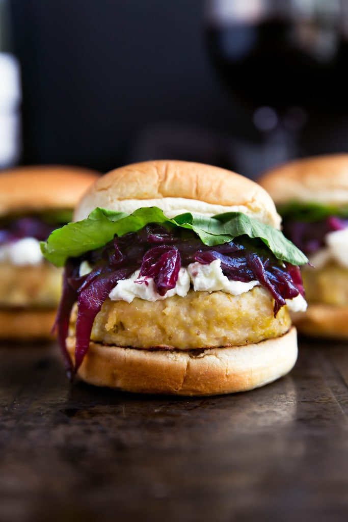 Say hello to these classy game-day buns: rosemary-infused turkey sliders topped with red wine caramelized onions, crumbled goat cheese, and arugula!