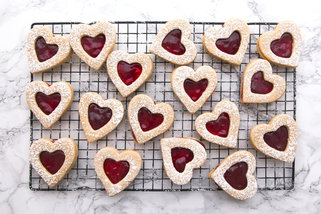 cherry linzer cookies on a wire cooling rack