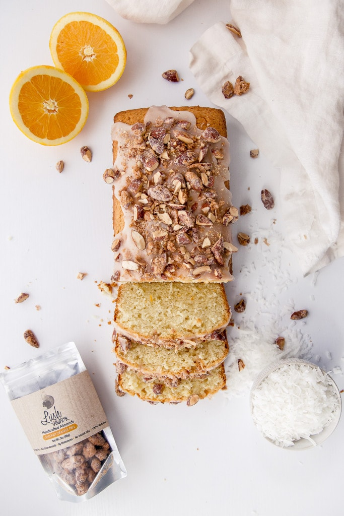 A tropical coconut orange bread topped with coconut glaze and candied coconut orange almonds!