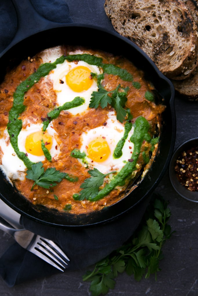 shakshuka (eggs in hell) in a cast iron skillet with bread slices