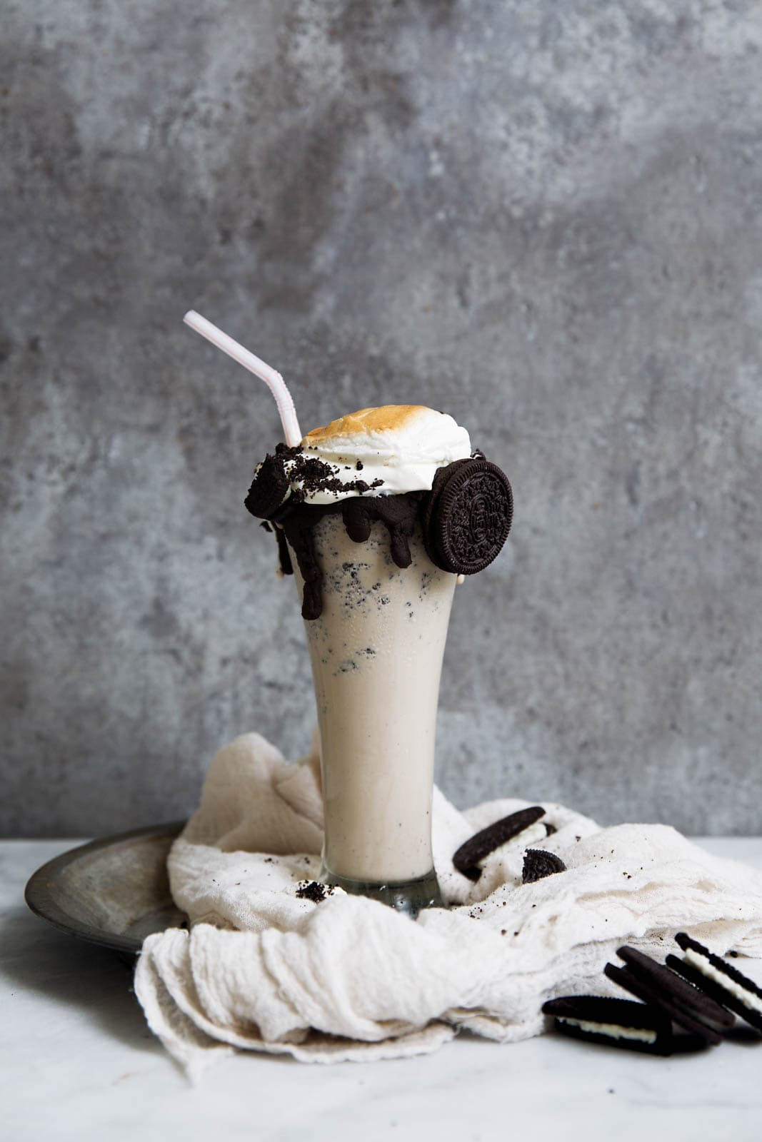 The ultimate Iced Coffee Cookies and Cream Milkshake, complete with chocolate sauce, whipped cream, and a giant toasted marshmallow