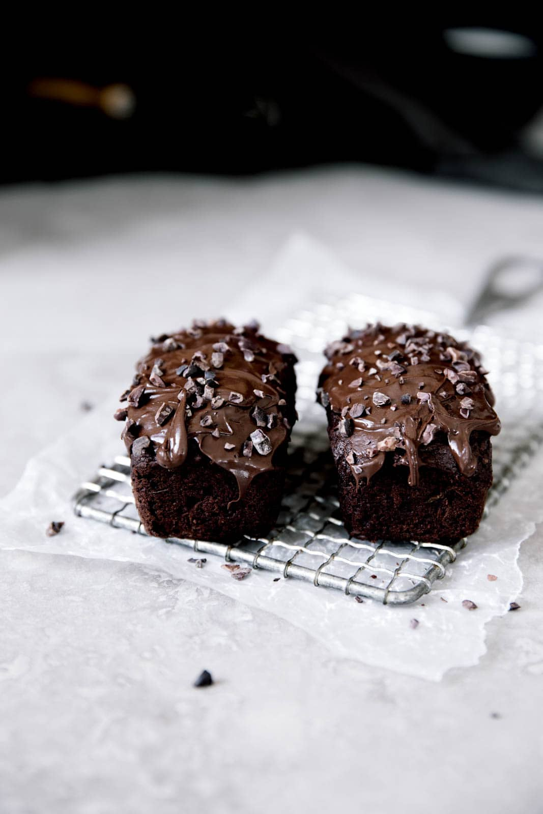 chocolate zucchini bread loaves topped with chocolate ganache and cacao nibs