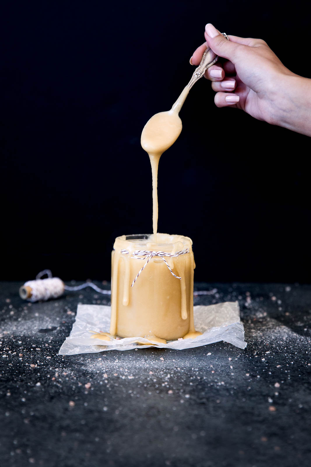 drizzling maple salted caramel sauce into a jar
