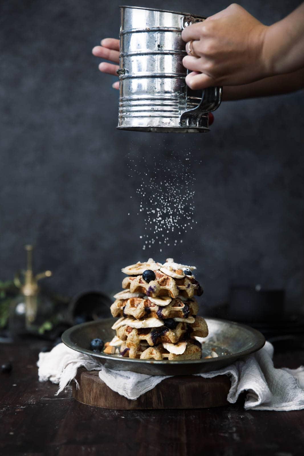 sprinkling powdered sugar onto gluten free waffles