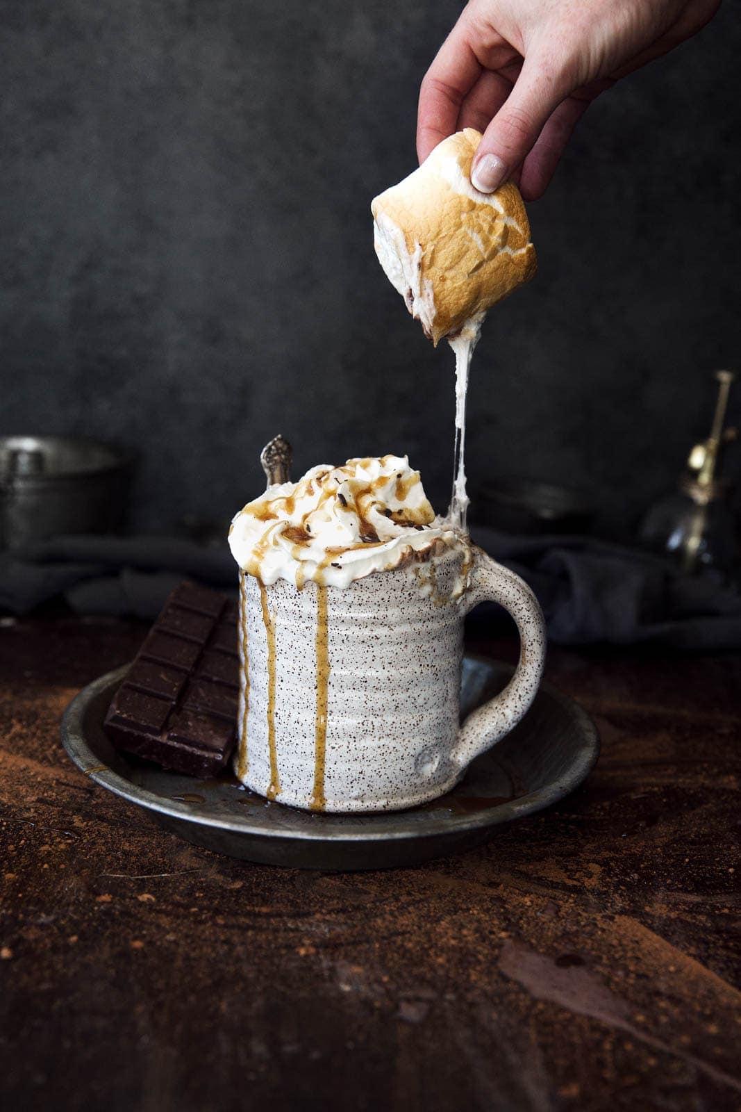 pulling a marshmallow off a caramel mocha