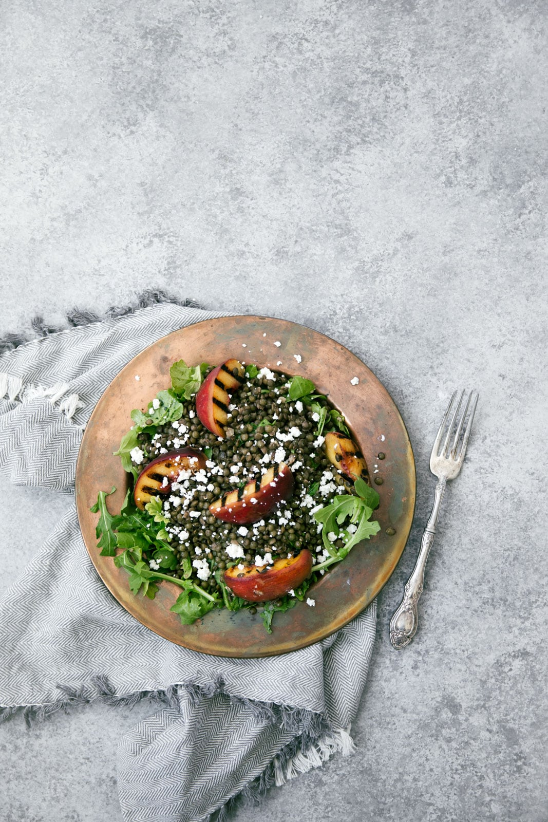 Take advantage of peach season with this green lentil salad with char-grilled peaches, goat cheese, and rosé vinaigrette.