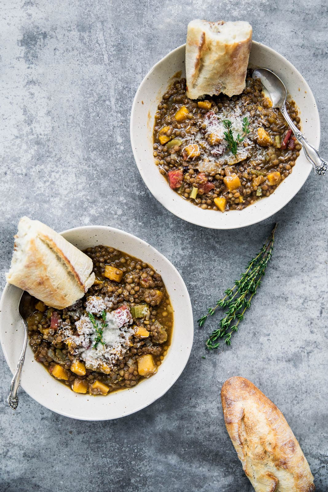 two bowls of butternut squash lentil stew with pieces of bread