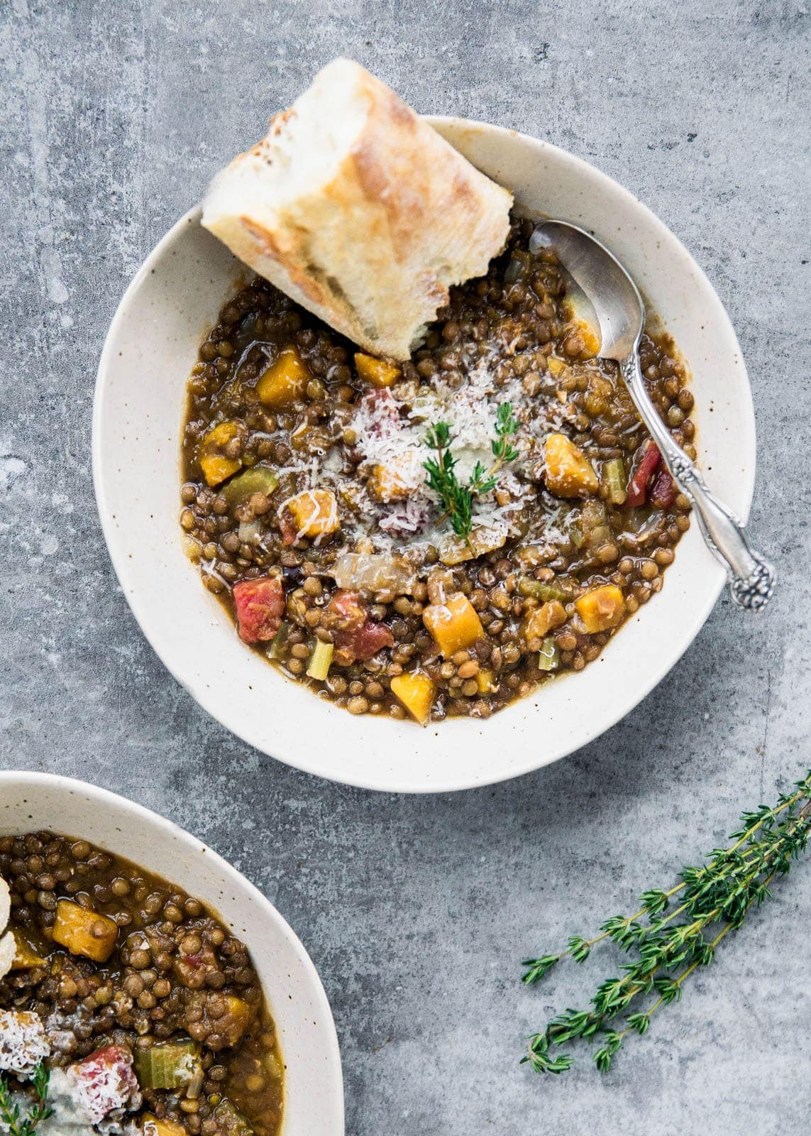 bowl of butternut squash lentil stew topped with cheese