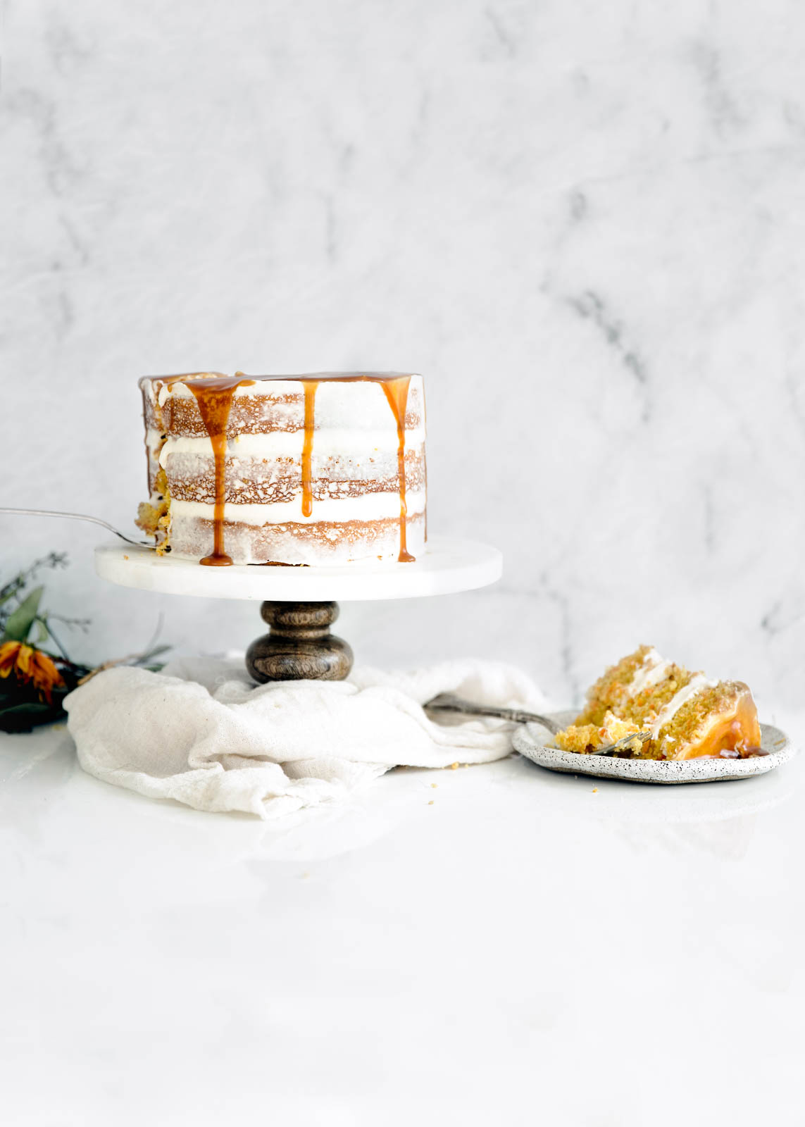 spiced carrot cake on cake stand next to slice of cake
