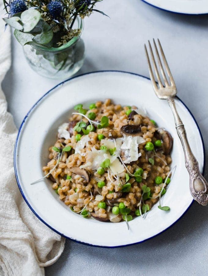 A warm and comforting farro risotto made with fresh spring peas and sautéed mushrooms!