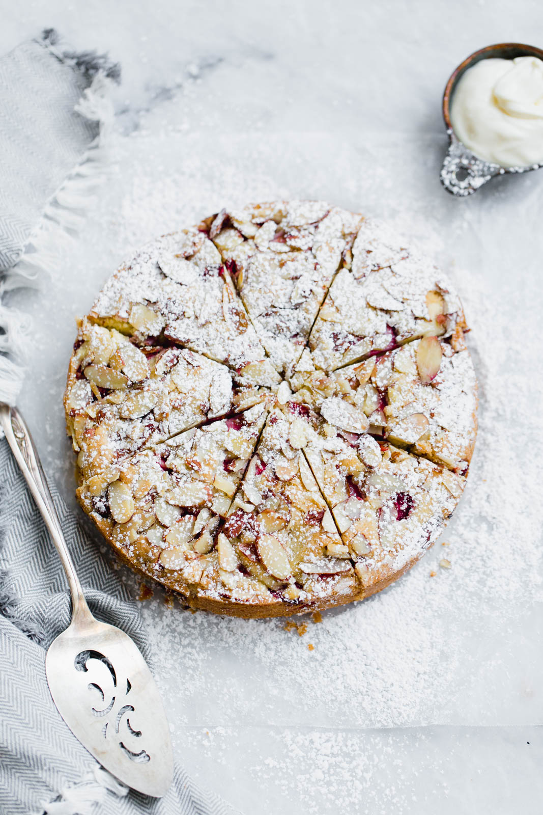 strawberry almond cake topped with slivered almonds and powdered sugar