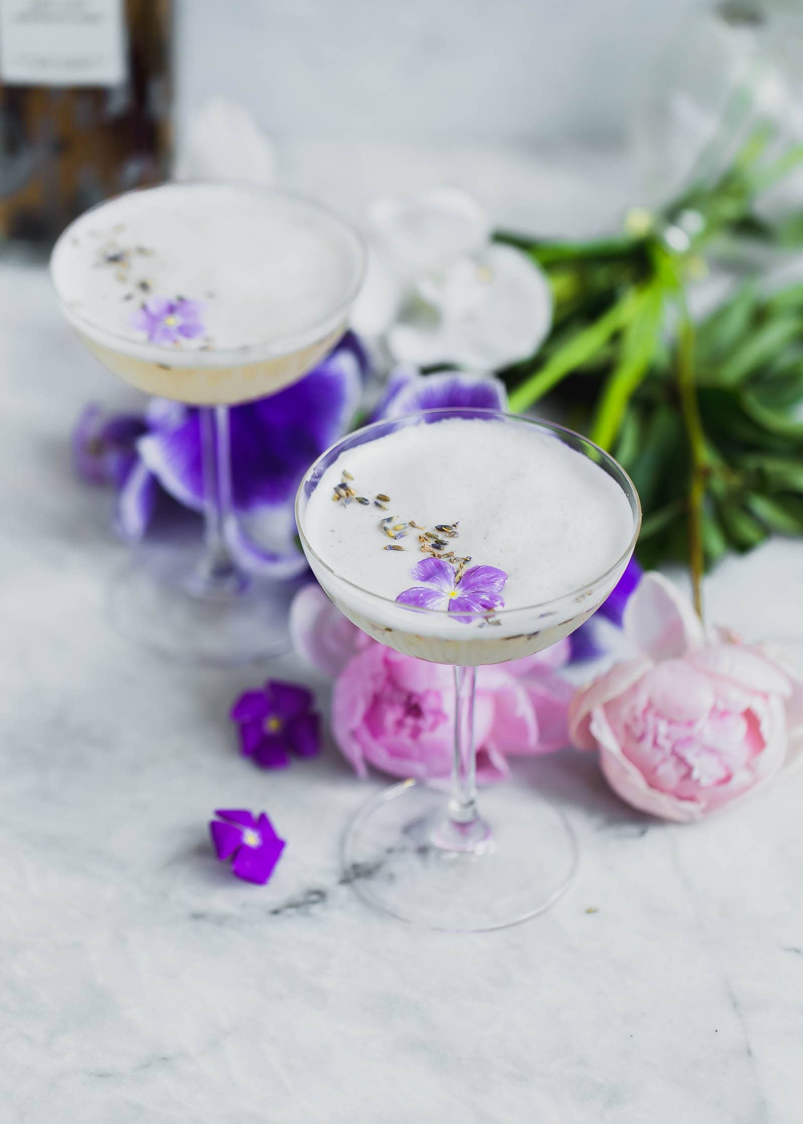 Lavender Coconut Vodka Sours topped with violets
