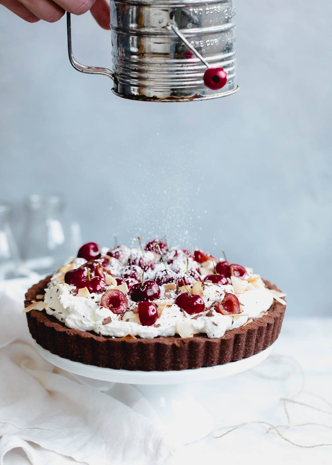A take on Black Forest Cake, this fudge-like chocolate cherry tart is topped with whipped cream, toasted coconut, and fresh cherries.