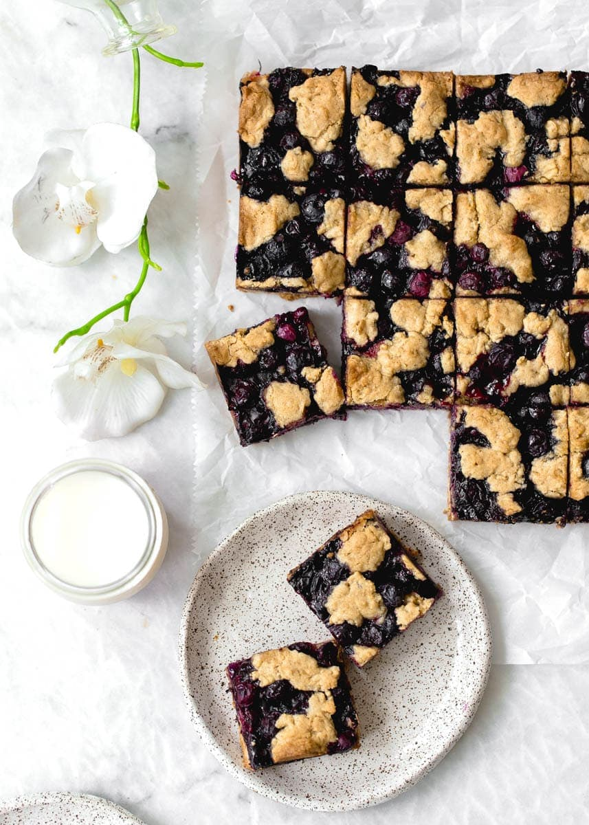 Whole Wheat Ginger Blueberry Crumble Bars with fresh blueberries. Perfect with a glass of cold milk.