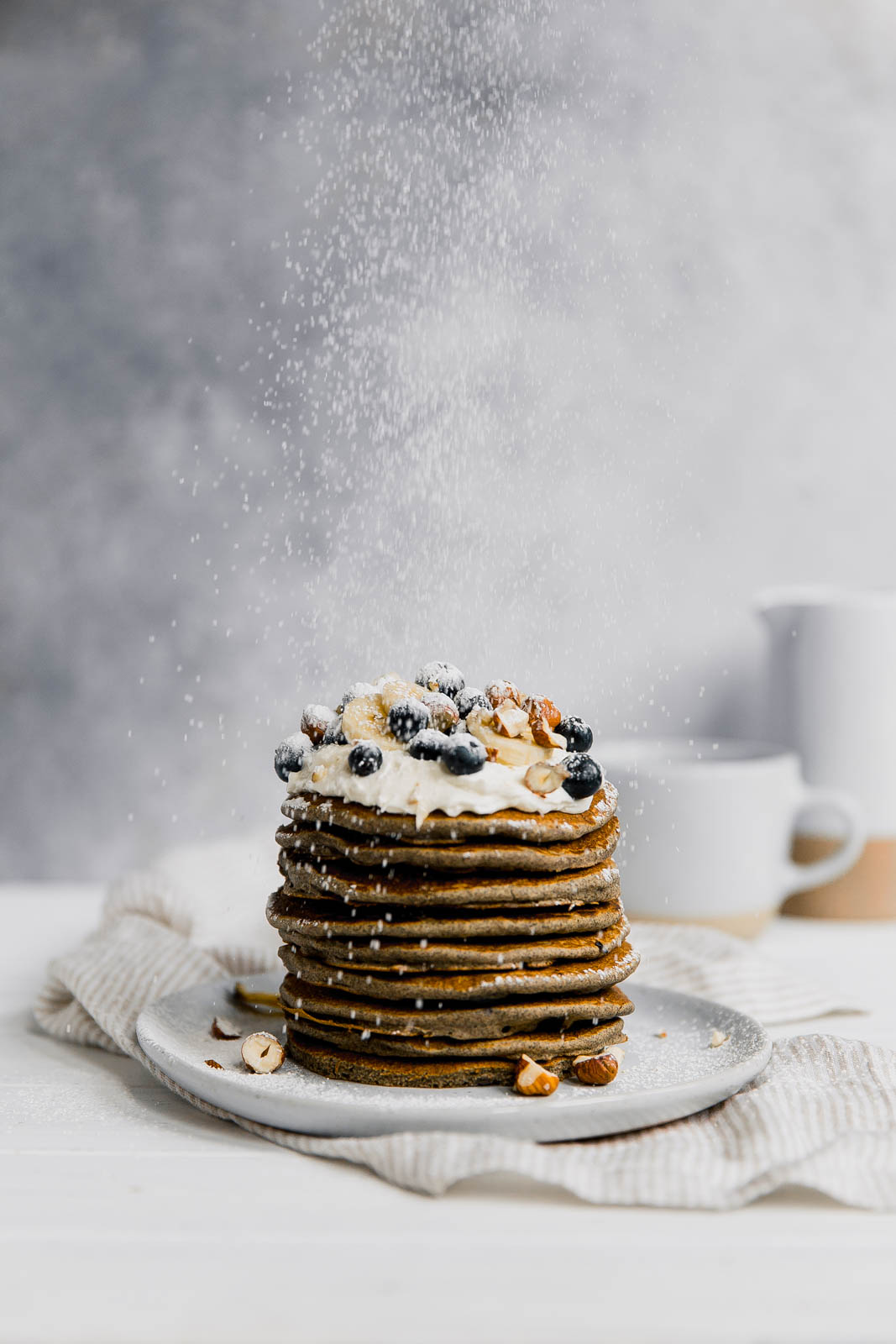 dusting powdered sugar onto gluten free buckwheat pancakes