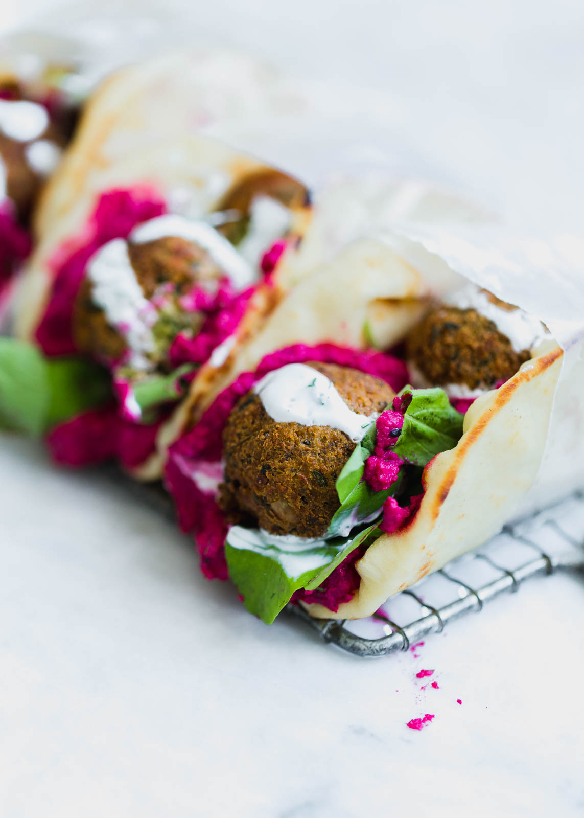 green falafel sandwiches topped with beet hummus and yogurt