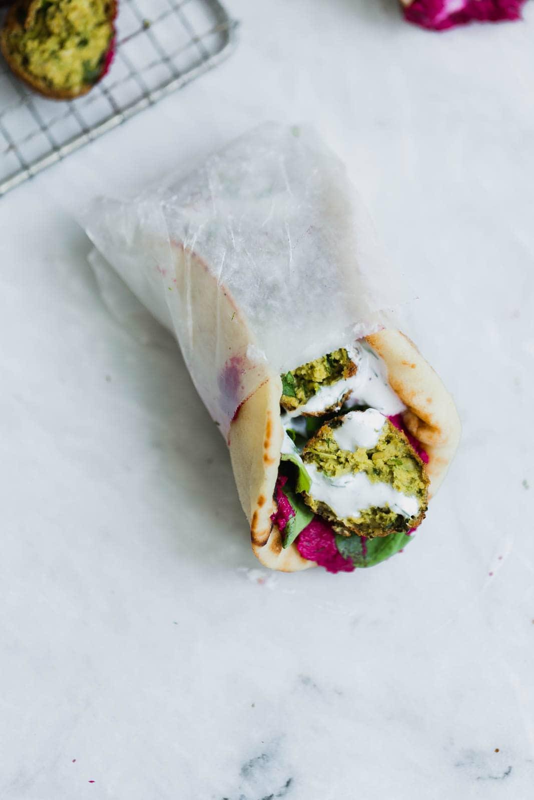 green falafel sandwich in wax paper