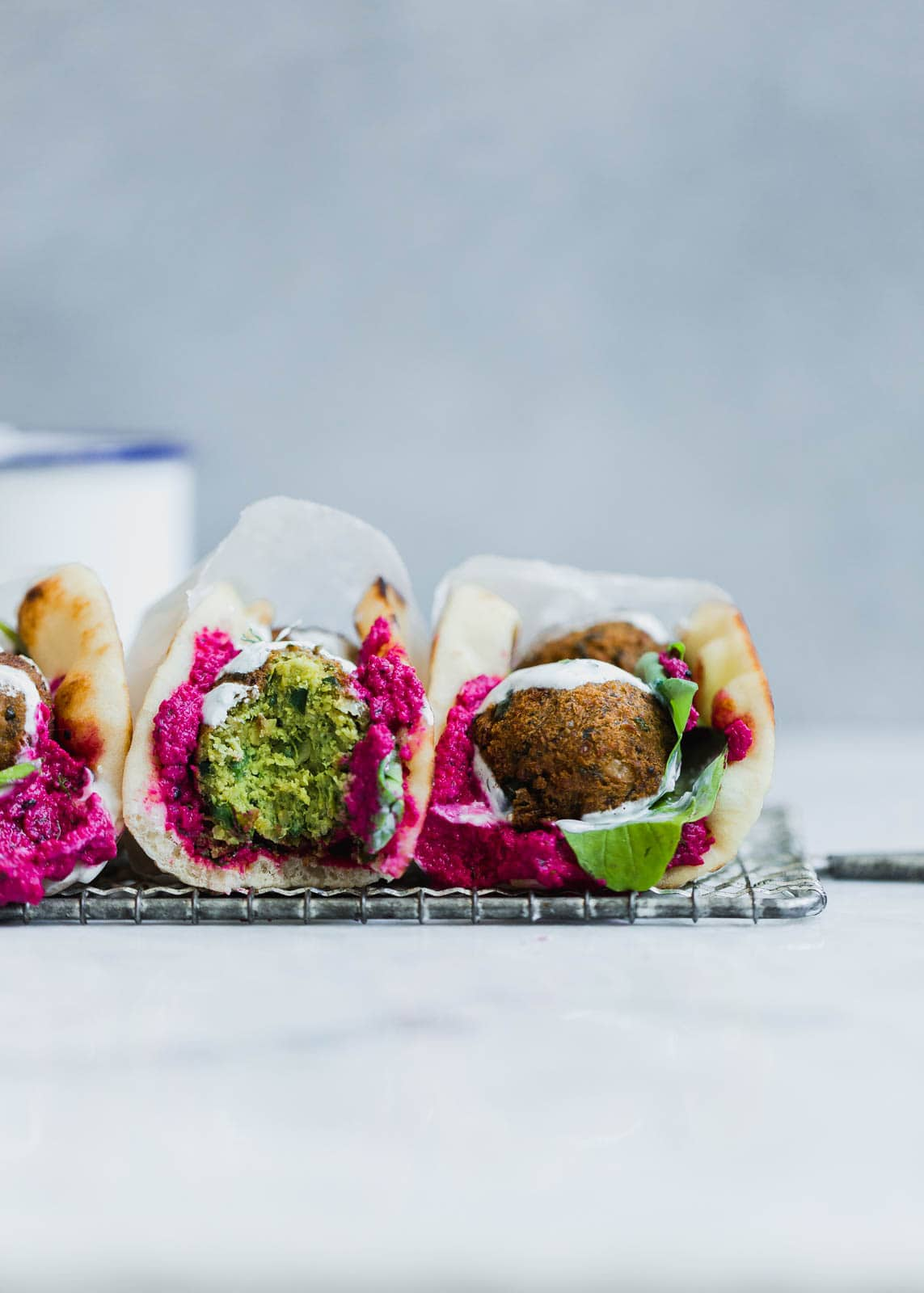 Homemade green falafel filled with spinach and garden herbs, smothered between beet hummus, yogurt, and pita.