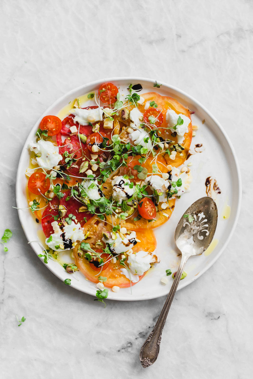 A raw Heirloom Tomato Carpaccio made with thinly sliced heirloom tomatoes, fresh burrata cheese, pistachios, corn, and microgreens.