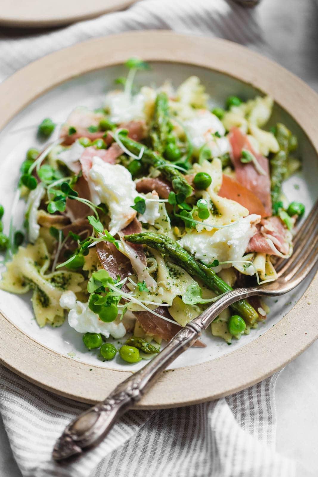 A sensational pasta salad with homemade pesto, prosciutto, peas, asparagus, and burrata.