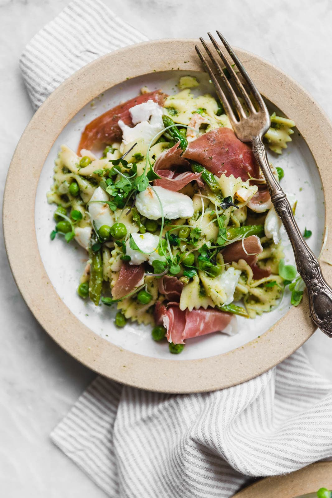 A sensational pasta salad with homemade pesto, prosciutto, peas, asparagus, and burrata.