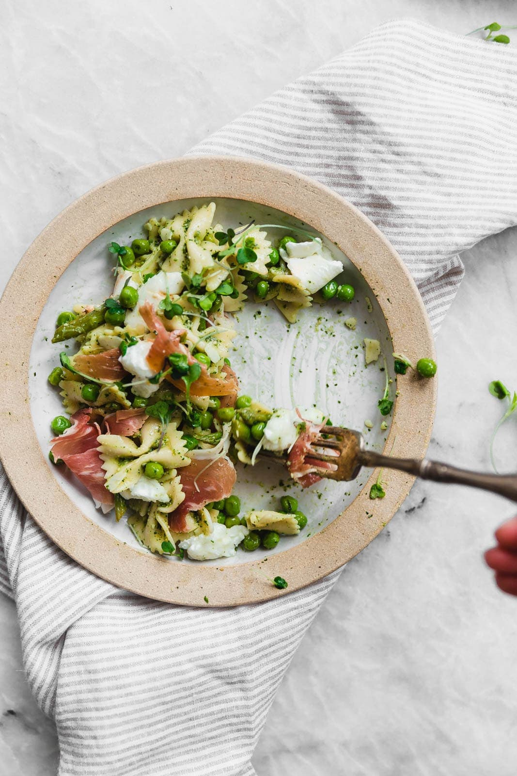 A sensational pesto pasta salad with homemade pesto, prosciutto, peas, asparagus, and burrata.