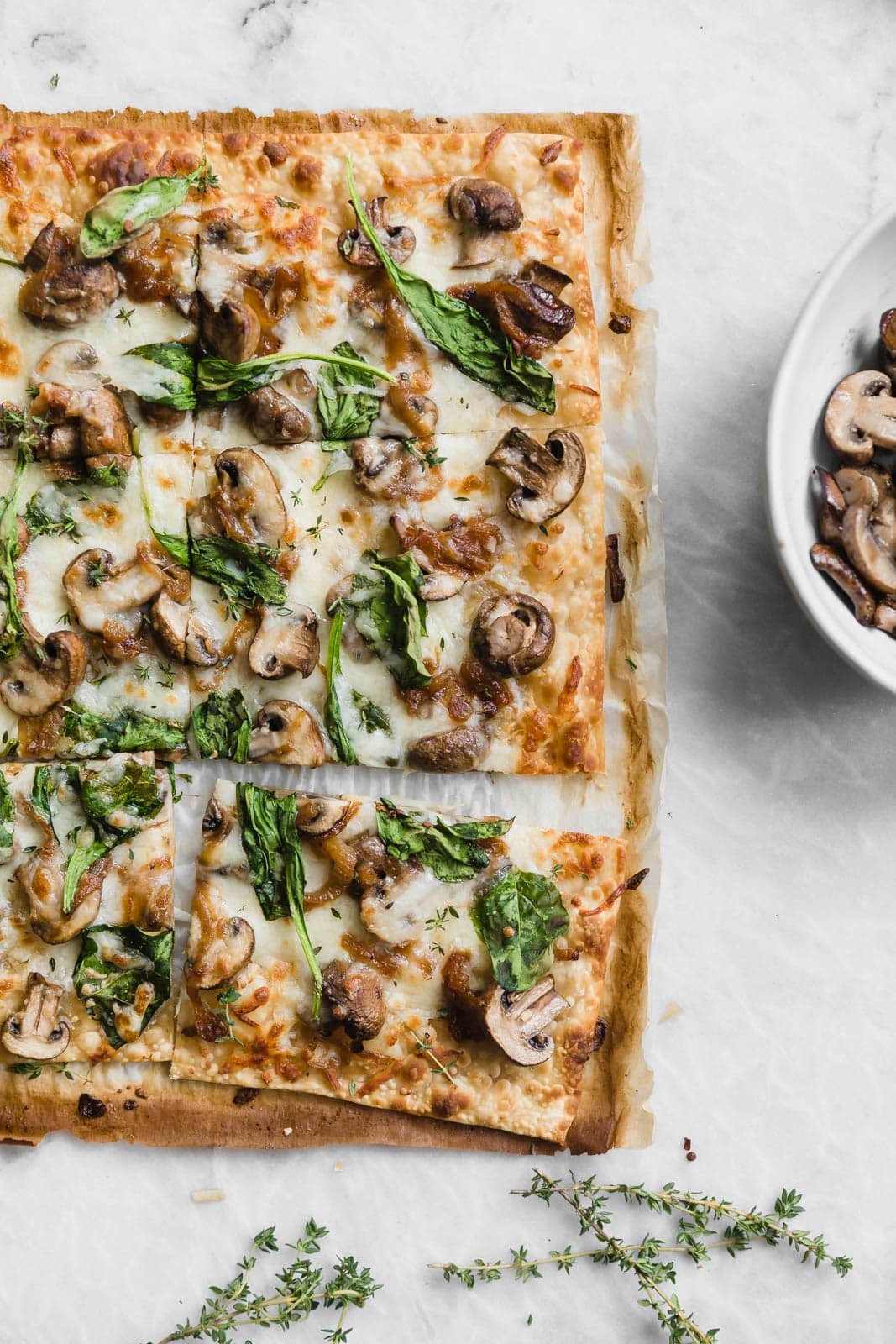 Caramelized Onion, Mushroom, & Spinach Pizza on marble countertop