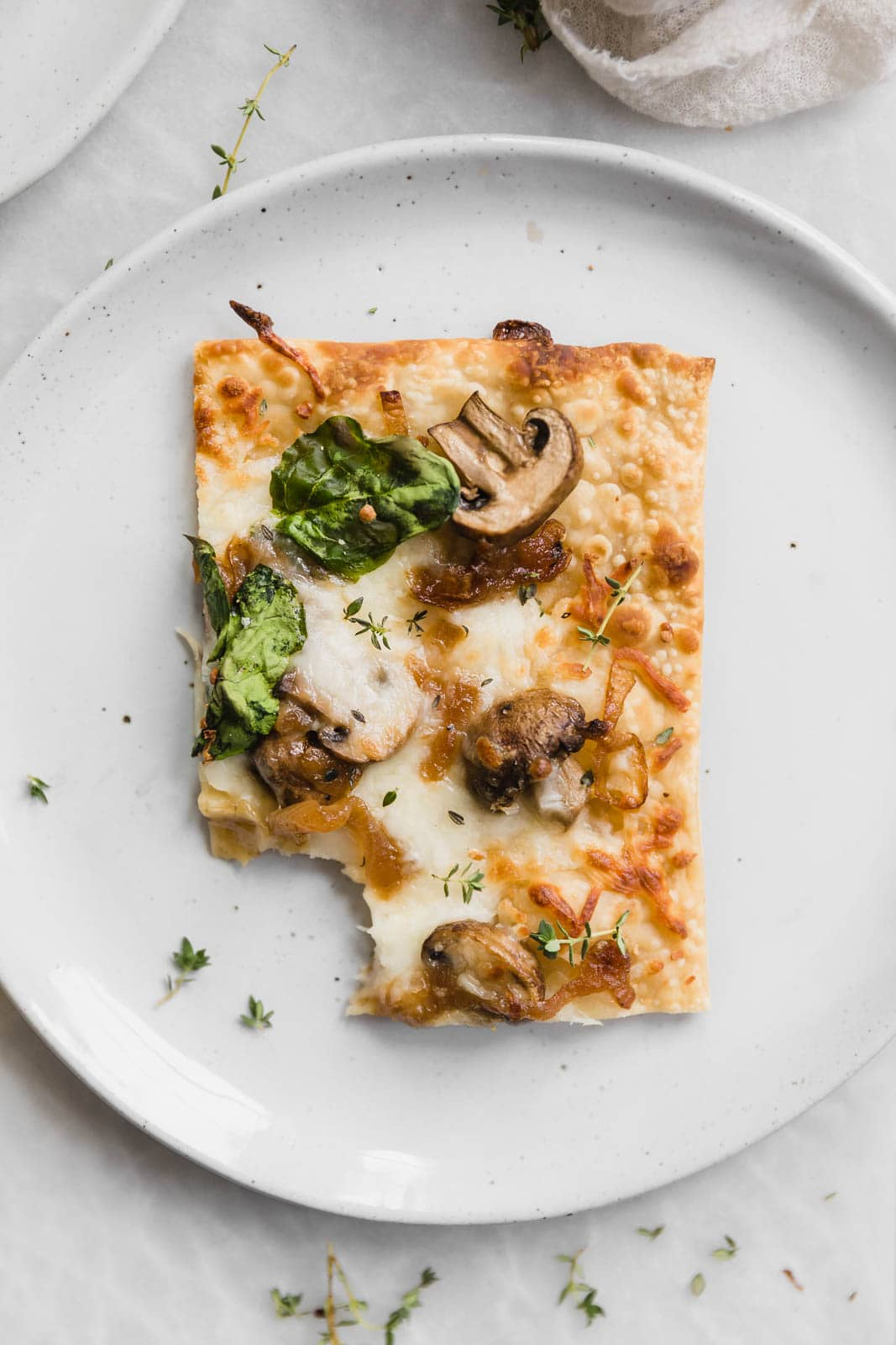 Caramelized Onion, Mushroom, & Spinach Pizza slice on a plate