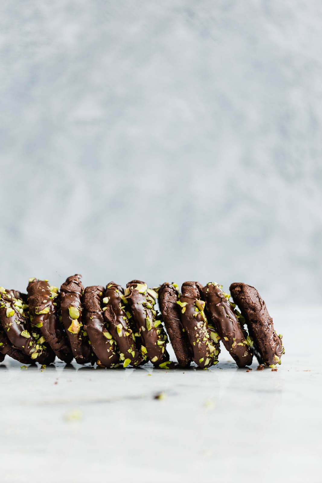 Delightfully rich and crunchy Chocolate Sable Cookies dipped in dark chocolate and coated in pistachio!