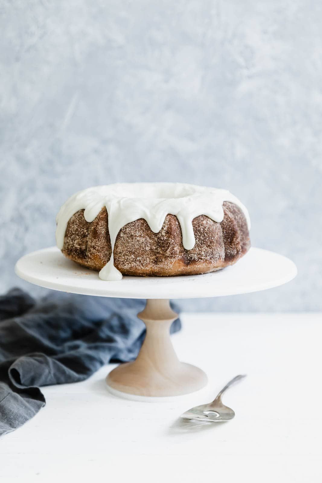 Cinnamon Bundt Cake on cake stand with spatula