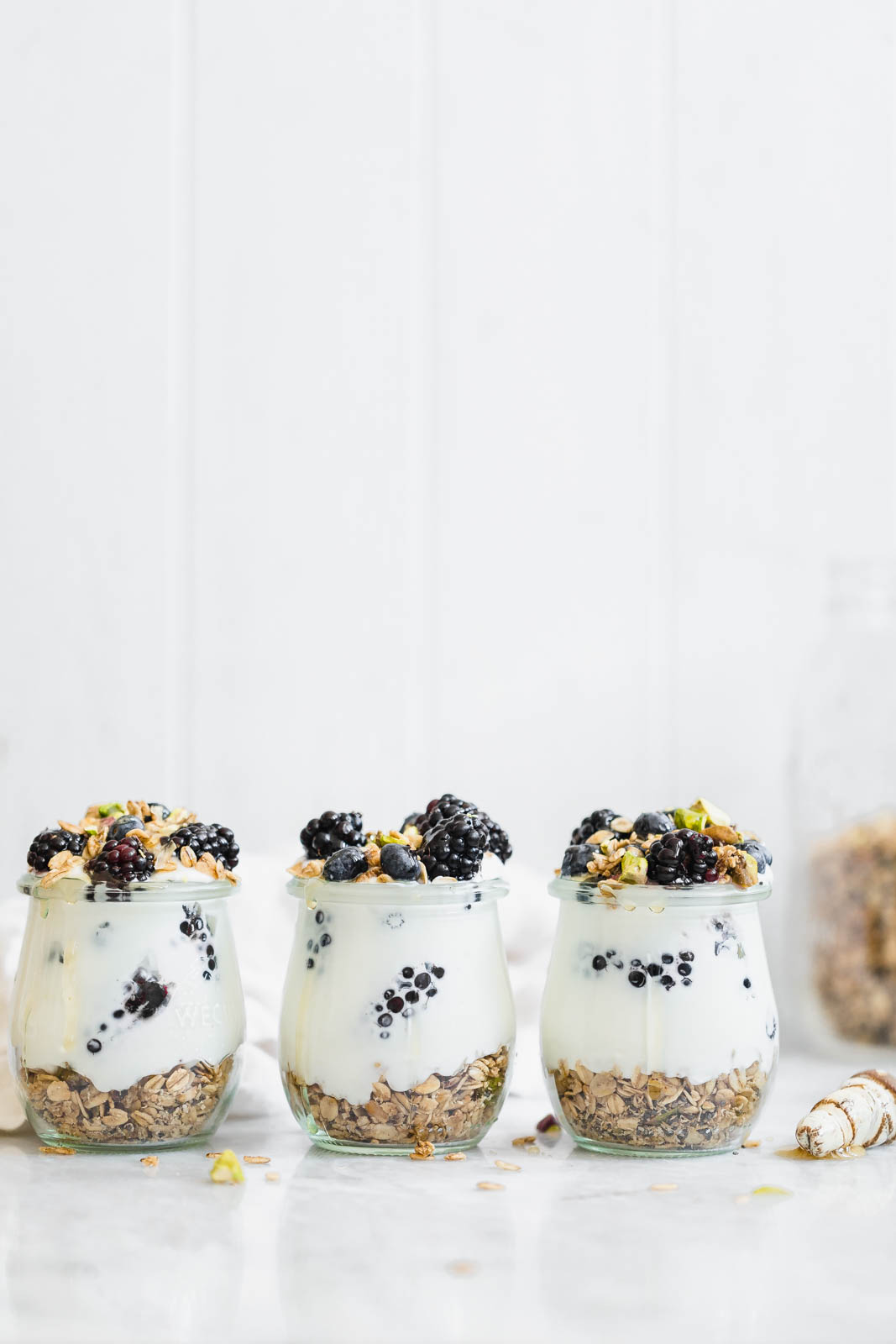 A chai-spiced Cardamom Granola Parfait made with the most addicting Cardamom granola, and topped with blackberries and honey.