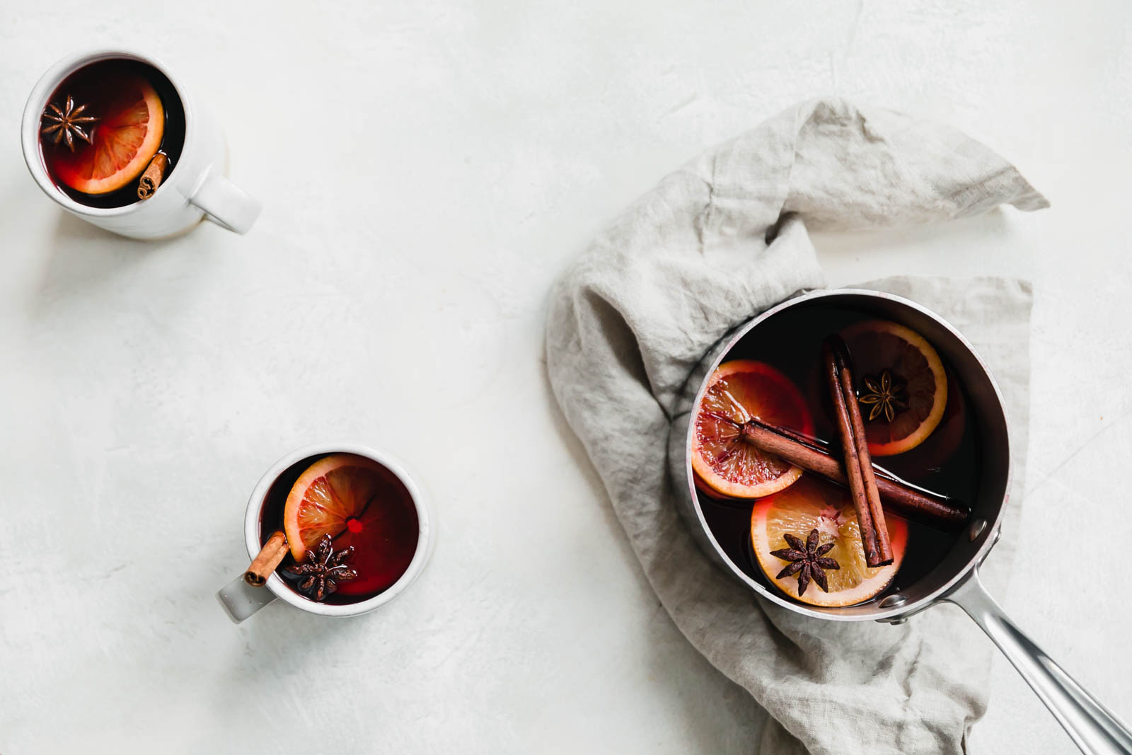 mulled wine in mugs and sauce pan