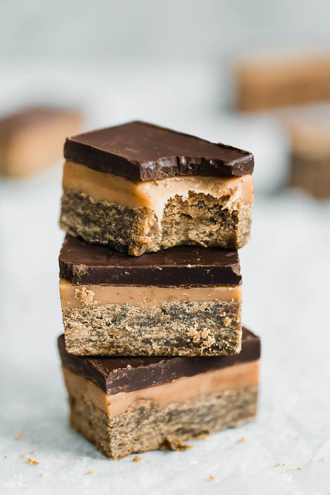 Classic Millionaire Bars get a twist with these Gingerbread Millionaire Bars! Made with spiced ginger shortbread, homemade chewy caramel, and chocolate!
