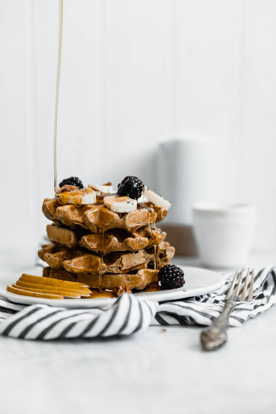 drizzling maple syrup onto pumpkin spice waffles
