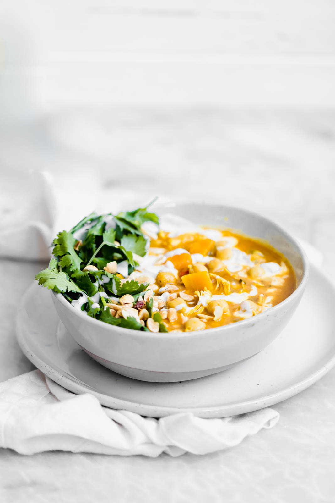 Turmeric Chicken Soup garnished with peanuts and cilantro