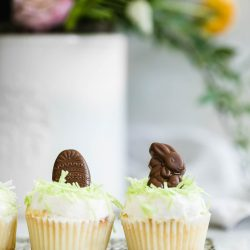 """Easter Bunny Cupcakes: a perfect vanilla cupcake topped with buttercream, green """"grass,"""" and caramel-filled chocolate Easter bunnies!"""