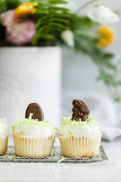 "Easter Bunny Cupcakes: a perfect vanilla cupcake topped with buttercream, green ""grass,"" and caramel-filled chocolate Easter bunnies!"