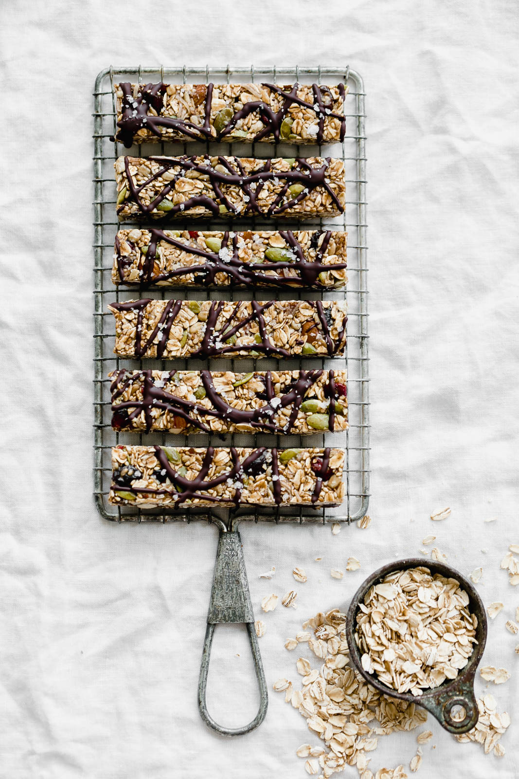 Raw Seedy Granola Bars made with oats, sunflower seeds, pepitas, sesame seeds, almonds, apricots, and honey, topped with a drizzle of dark chocolate