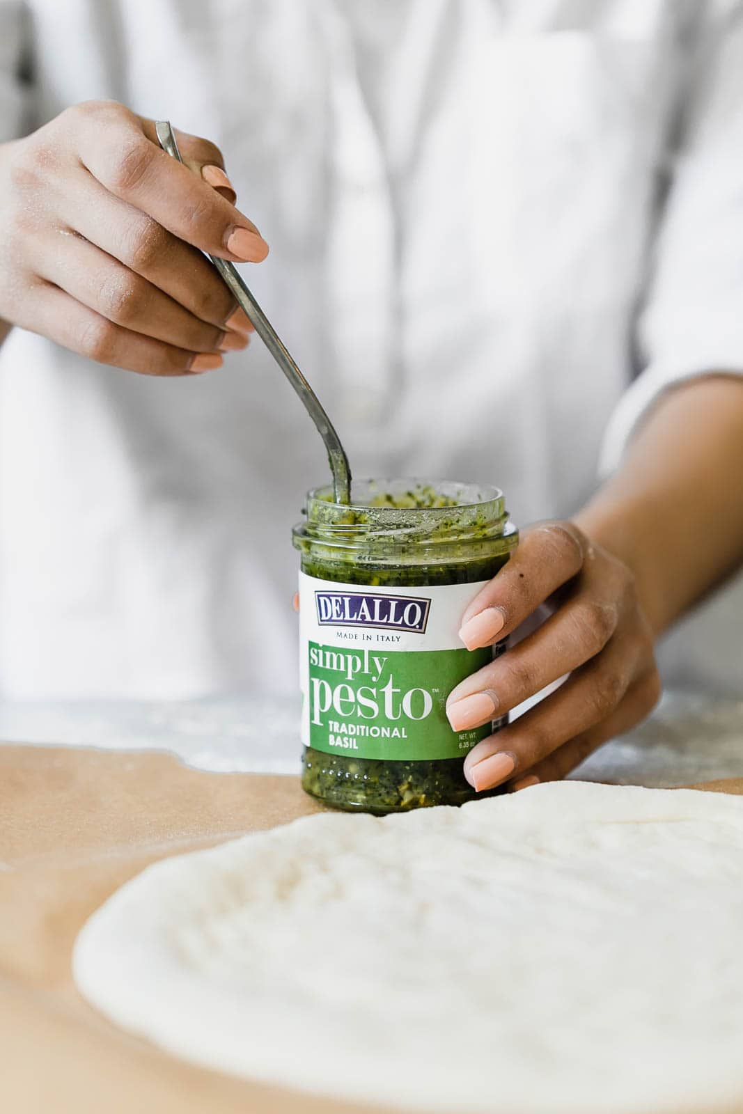 A Spring Green Goddess Pizza made with pesto, zucchini, spring peas, watercress, mozzarella, and a green goddess dressing.