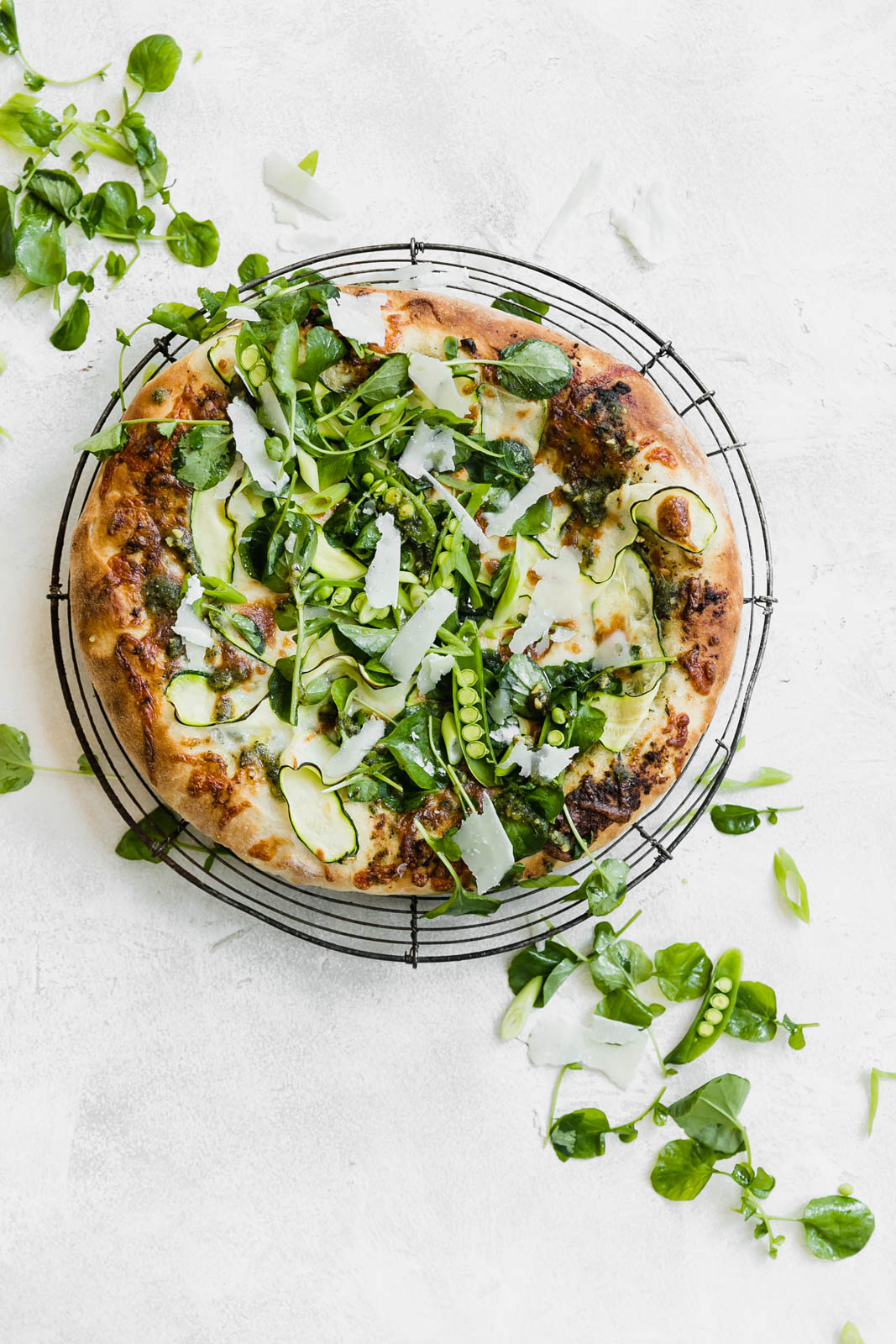 A Spring Green Goddess Pizza made with pesto, zucchini, spring peas, watercress, mozzarella, and a green goddess dressing.
