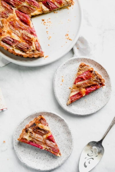 The most showstopping Rhubarb Bakewell Tart made with a pâte sucrée crust, strawberry preserves, almond frangipane, and an orange-soaked rhubarb top