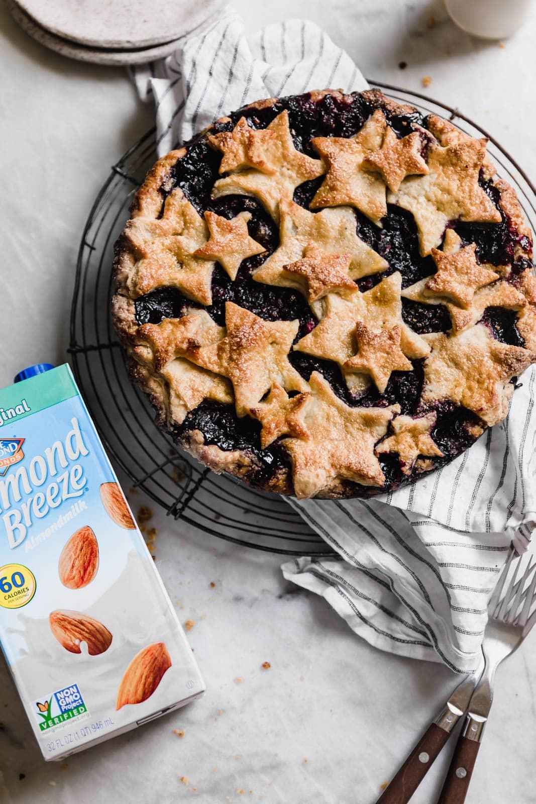 blueberry pie next to carton of almond milk